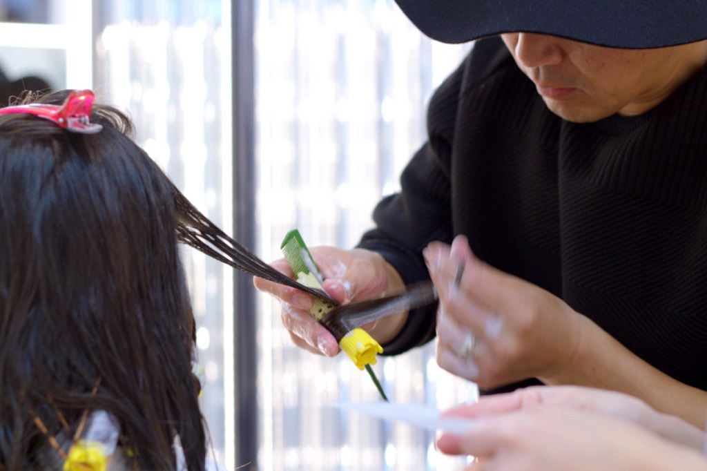 Salón paquete ANTI - Imagen 4 - estilistas que aplican la solución permanente en el cabello